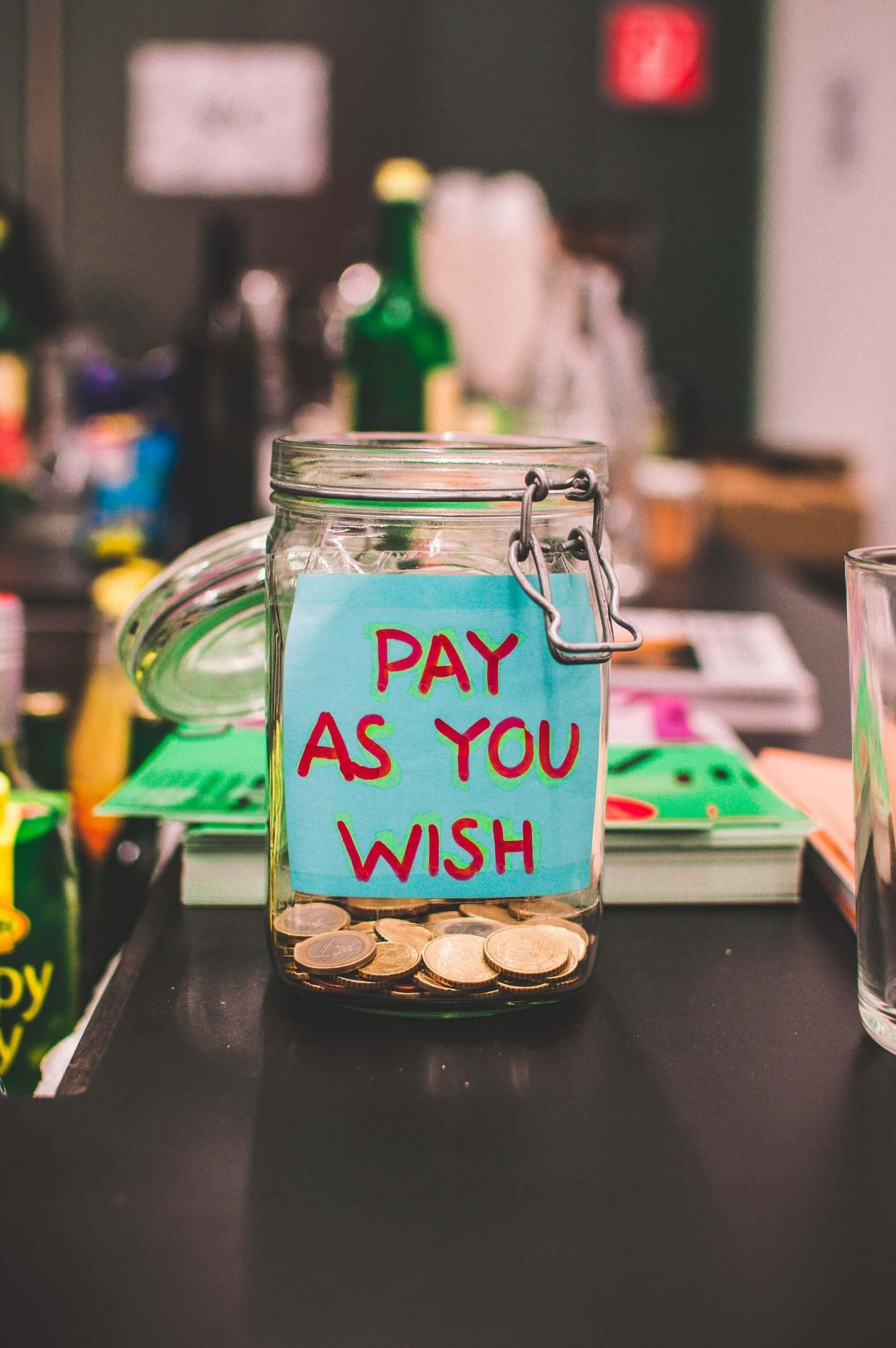"""A money jar with a sign saying """"pay as you wish"""" - Monetize Your YouTube Channel"""