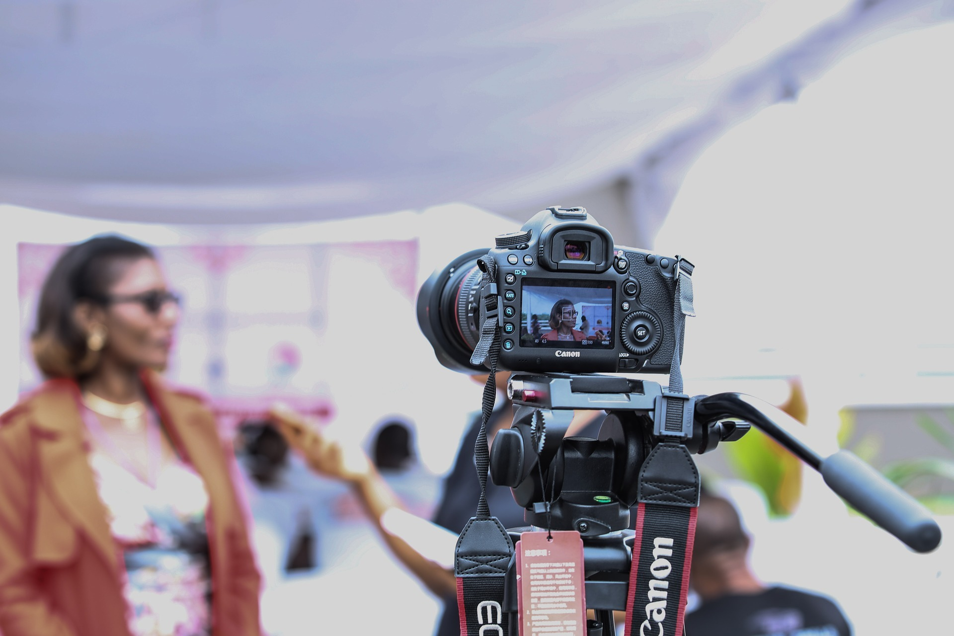 Canon camera recording a woman being interviewed