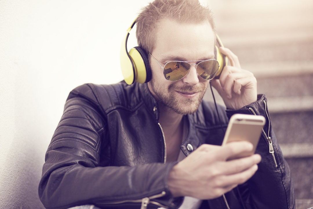 Man listening to something via headphones- Business Podcasts